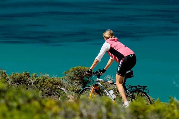 Ciclista pedala tra la vegetazione vicino al mare