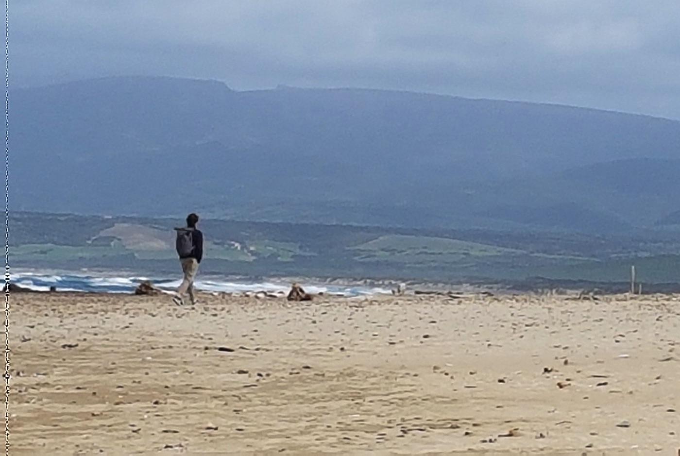 un uomo cammina lungo una spiagga nei dintorni di Capo Mannu nel Sinis